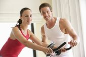 pic of exercise bike  - Young Couple On Exercise Bike - JPG