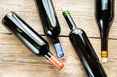 stock photo of shiraz  - Bottles With Red Wine On The Wooden Table - JPG