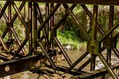 foto of old bridge  - Old rusty abandoned steel bridge over the river - JPG