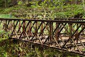 stock photo of old bridge  - Old rusty abandoned steel bridge over the river - JPG