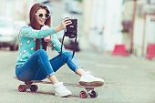 Постер, плакат: Beautiful young woman posing with a skateboard fashion lifestyle at sunset