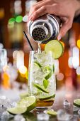 picture of mojito  - Mojito cocktail drink on bar counter with barman holding shaker on background - JPG