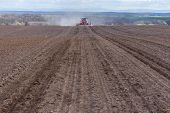 pic of cultivator-harrow  - The tractor harrowing the large brown field in spring season - JPG