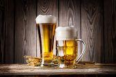 image of beer mug  - Tall glass and mug of light beer with ears barley on wooden background - JPG