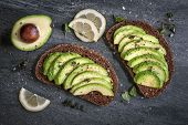stock photo of fresh slice bread  - Avocado sandwich on dark rye bread made with fresh sliced avocados from above - JPG