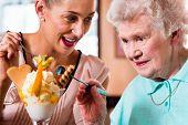 pic of granddaughters  - Senior woman and granddaughter having fun eating ice cream sundae in cafe - JPG