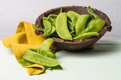 pic of snow peas  - Snow peas on wooden bowl with green napkin on wooden table.