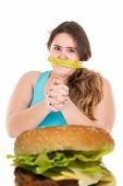 stock photo of gag  - Beautiful large girl gagged with measuring tape lokking at a burger isolated in white - JPG