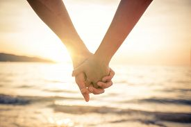 stock photo of couple  - Couple of lovers holding their hands at a beautiful sunset over the ocean  - JPG