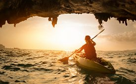 image of kayak  - Young lady paddling the kayak in a sea near the cave exit - JPG