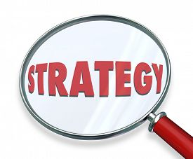stock photo of objectives  - Strategy word under magnifying glass to illustrate evaluating - JPG