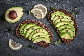 stock photo of fresh slice bread  - Avocado sandwich on dark rye bread made with fresh sliced avocados from above - JPG