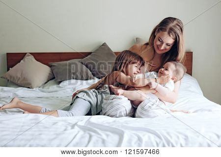 Young mom with her 5 years old daughter and 4 months old baby dressed in pajamas are relaxing and pl