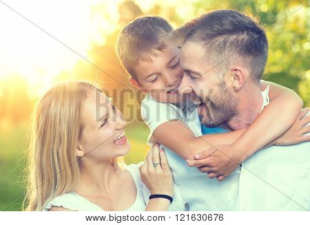 Happy young family having fun outdoors. Joyful young family father, mother and little son playing to