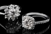 Luxury jewellery. White gold or silver engagement rings with diamonds closeup on black glass backgro poster