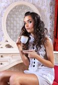 sad young woman sitting on armchair drinking tea