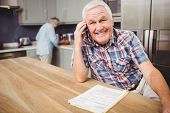 Senior man talking on phone and woman working in kitchen at home poster