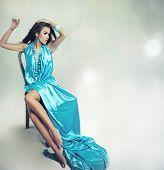 Постер, плакат: Молодая брюнетка красавица позирует на фоне студия