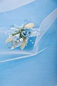 Wedding floral buttonhole with pearls on blue background and veil