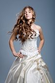foto of woman glamour  - Slim beautiful woman with long hair wearing luxurious wedding dress over gray studio background - JPG