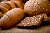 Various kinds of fresh tasty bread on sacking