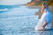 Bride wearing wedding dress running away from sea waves at coastline