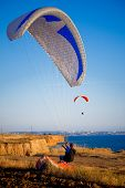Two paragliders in sky above sea coastline