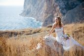 picture of field_stone  - Beautiful bride sitting on stone at field over mountains and sea coast landscape - JPG