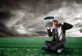 businessman with laptop under a storm