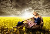 stock photo of pretty girl  - pretty girl sited on armchair in a field of yellow flowers - JPG