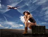 girl seated on a suitcase and a flying airplane