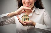 Mujer sonriente que sostiene el modelo de una casa