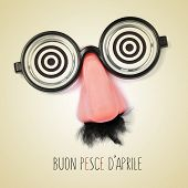 fake eyeglasses, nose and mustache and the sentence buon pesce d aprile, happy april fools day writt poster