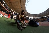 KUALA LUMPUR - AUGUST 16: Thailand's amputee runner prepares his running prosthesis at the track and