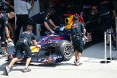 KUALA LUMPUR - APRIL 2: Red Bull team mechanics push Sebastian Vettel's car back into the garage on