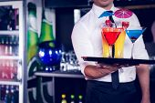 Mid section of bartender serving cocktail and martini at bar counter poster