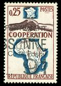 vintage French stamp depicting a black and white man shaking hands in cooperation between Africa and france