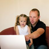 Father teaching his daughter how to use a laptop computer