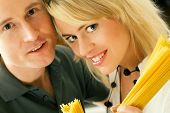 A couple with uncooked spaghetti (going to prepare them presumably)