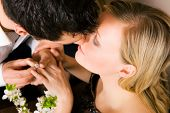 He is offering her the ring, she seems to be accepting with a kiss; focus on eyes