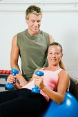 Woman lifting dumbbells on a fitness ball in a gym assisted by her personal instructor