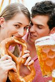 Couple in traditional German costume in a beer tent, he is having a drink, she a pretzel