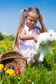 Child hunting the Easter bunny on a spring meadow, eggs in a basket and lots of flowers also to be s