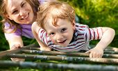 Little boy and his mother climbing up a ladder from a meadow, they want to reach their tree house (h