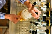 foto of drawing beer  - Man drawing a beer from tap on a kegerator in pub or inn - JPG