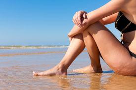 foto of monokini  - Attractive Woman in monokini sitting in the sun on beach - JPG