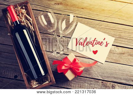 poster of Valentines day greeting card. Red wine and gift box on wooden table. Top view with copy space