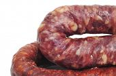 closeup of a spanish chorizo and a spanish fuet on a white background