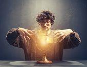Young man gazing at the glowing crystal ball. Predicting the future. Crystal gazing. Magic. poster