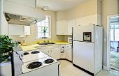 old dated kitchen with white appliances and yellow counters